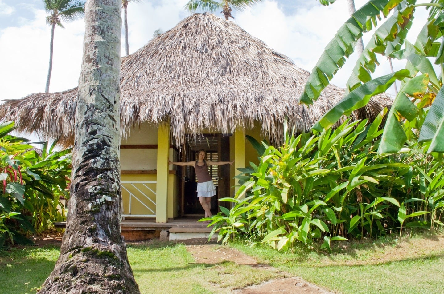 woman standing in thatch bungalow