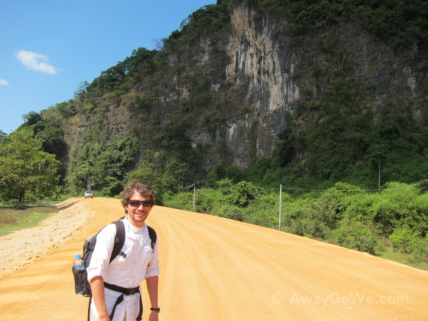 standing along the dirt road to buddha cave on the thakhek loop in laos