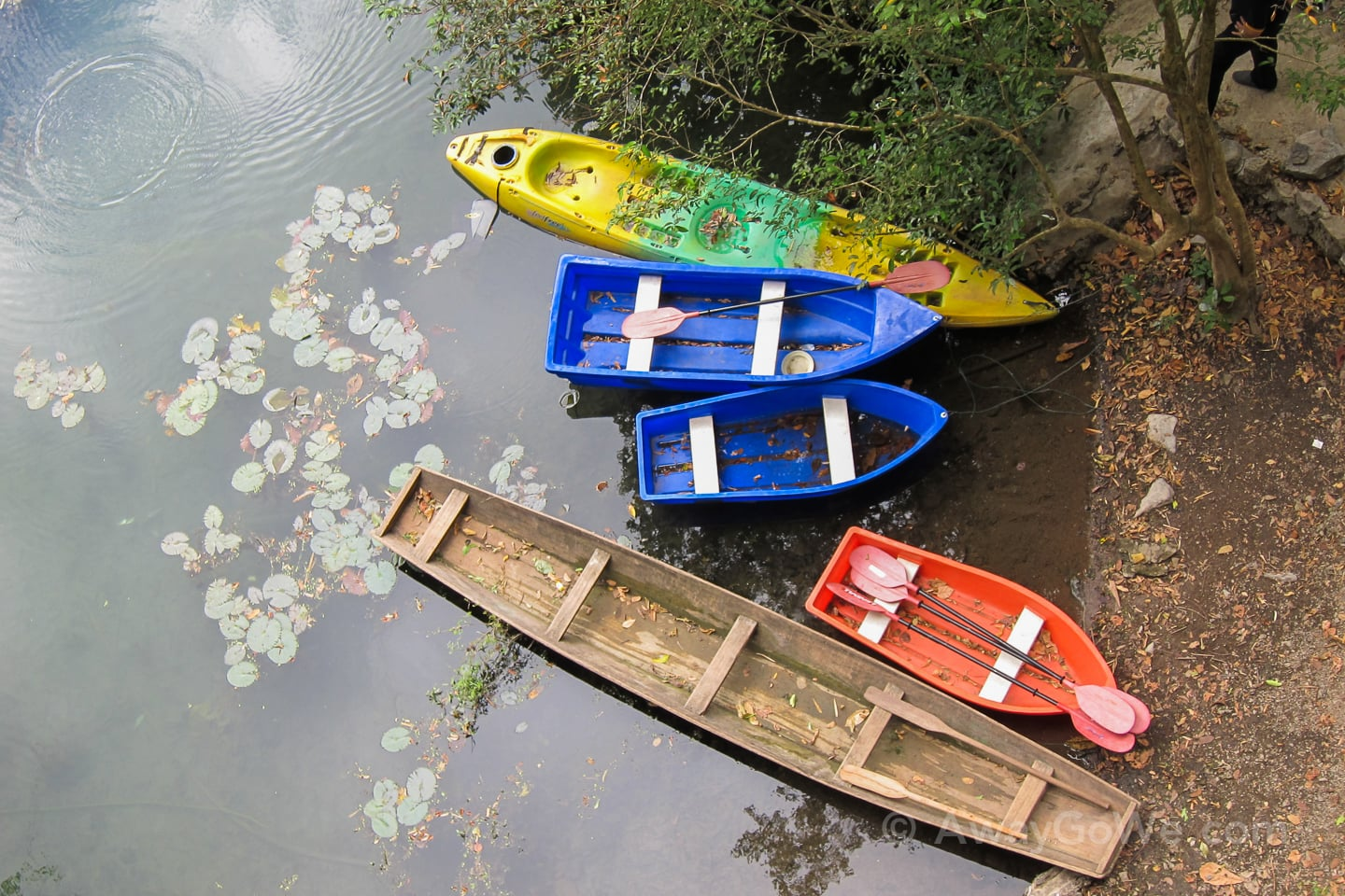 wooden and plastic boats near buddha cave