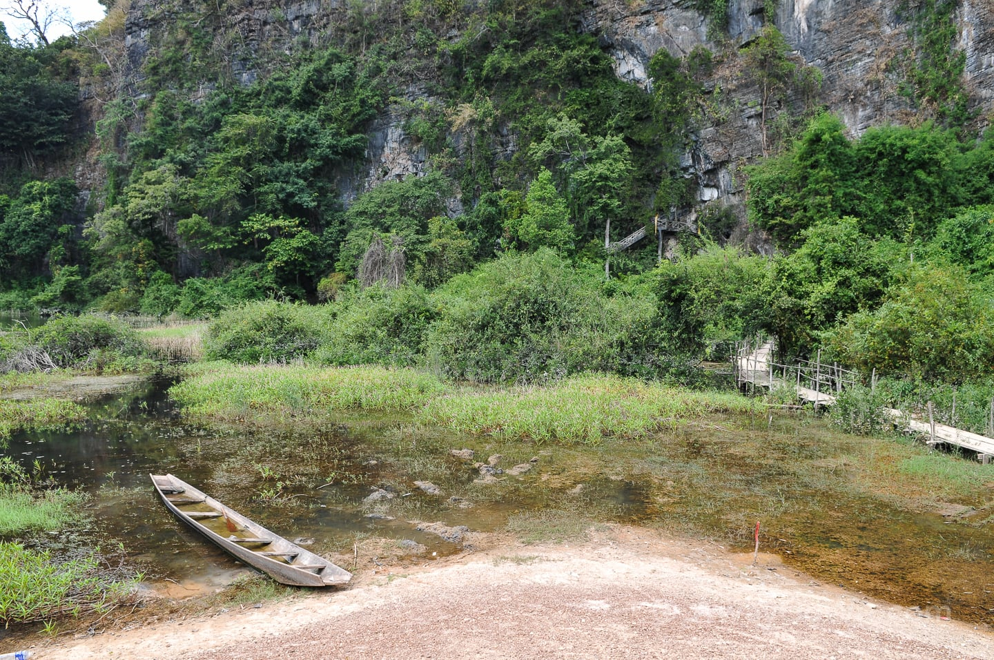wooden boat in pond near buddha cave along the thakhek loop route