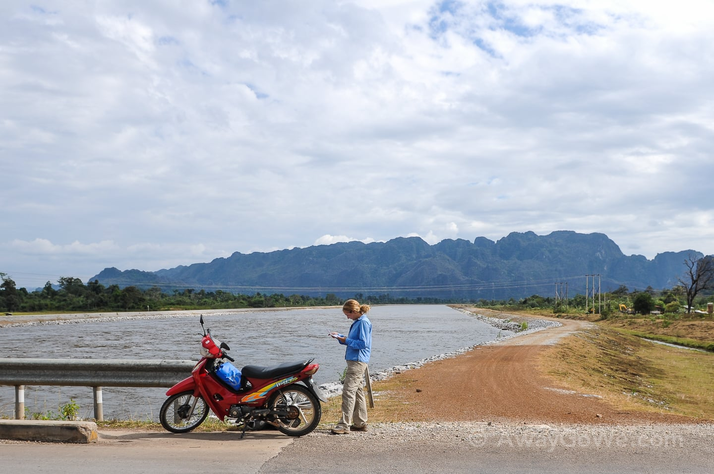 standing near motorbike on a bridge in laos