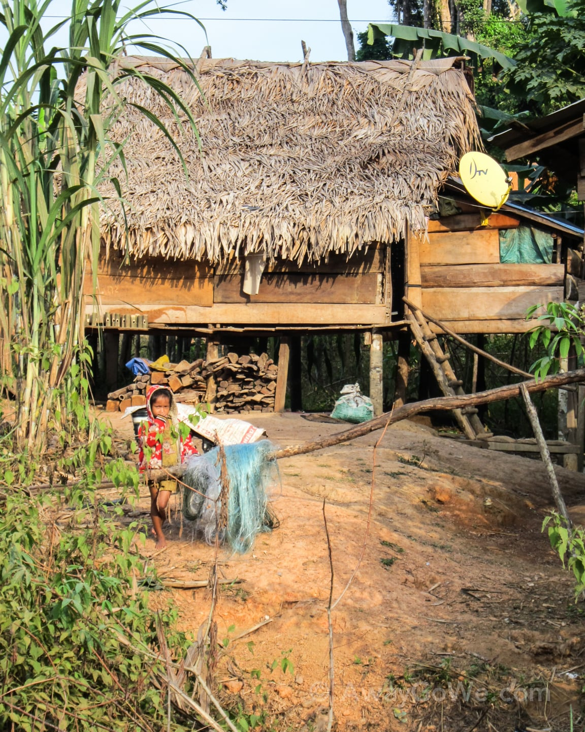 young girl standing in front of traditional wood and thatch house in laos