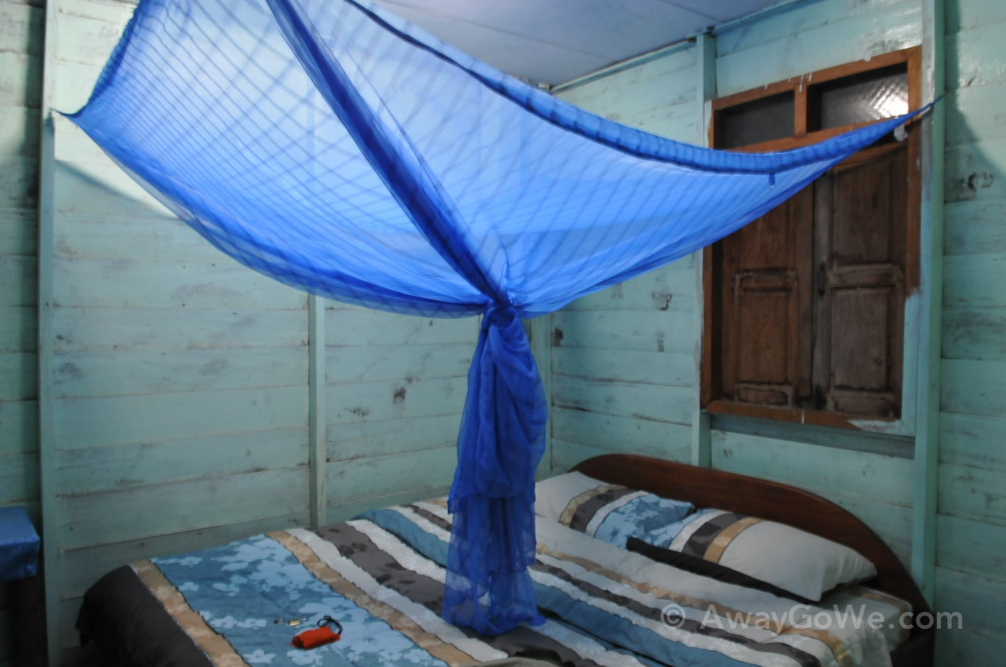bed and net inside wooden bungalow in laos