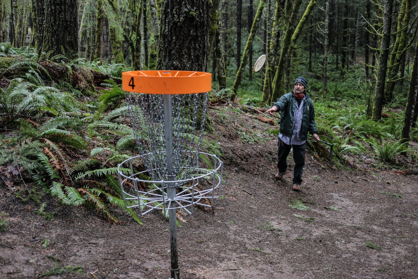 man playing disc golf in the Pacific Northwest woods