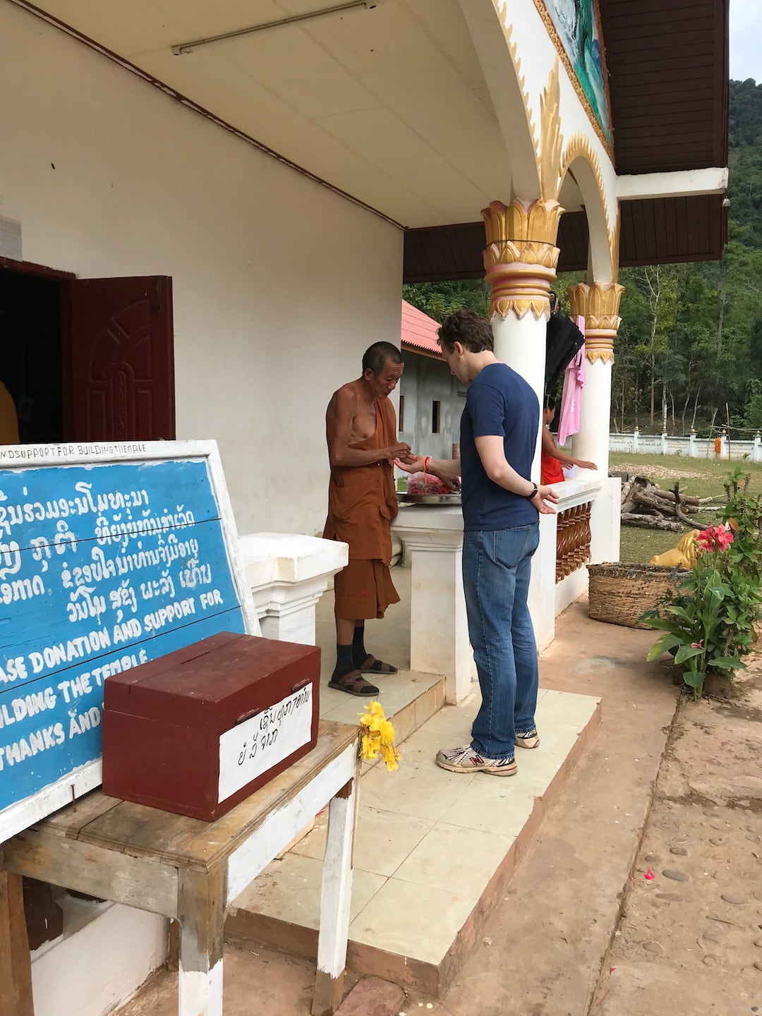 receiving a blessing from a Buddhist monk in Muang Ngoi Neua