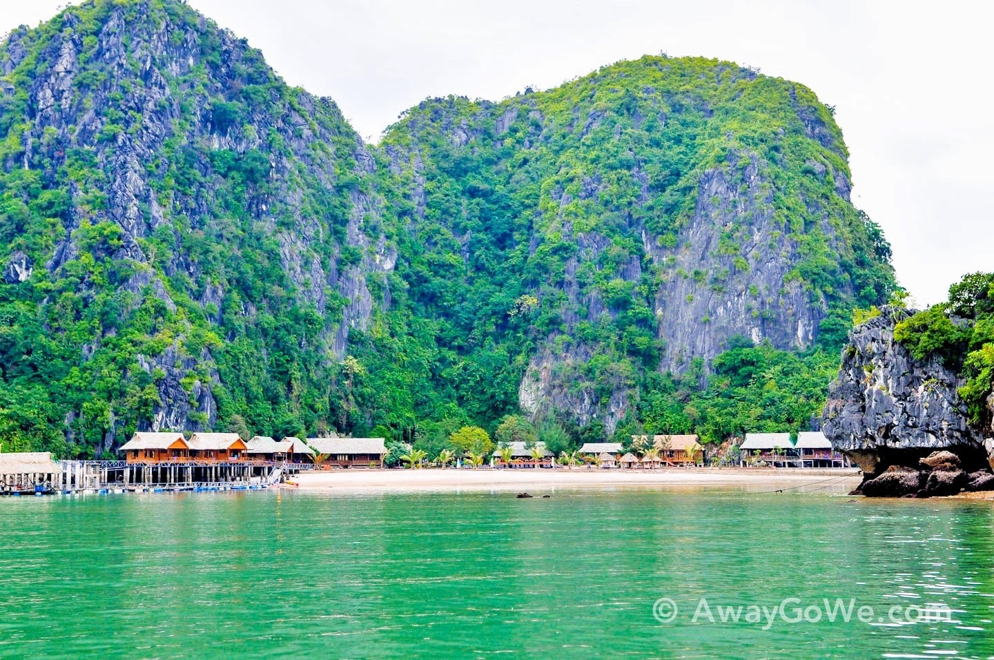 stilted bungalows on beach with karst cliff backdrop